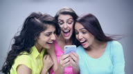 Three young women chatting on a mobile phone