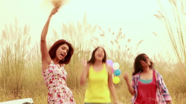 Three young women dancing in the forest, Delhi, India