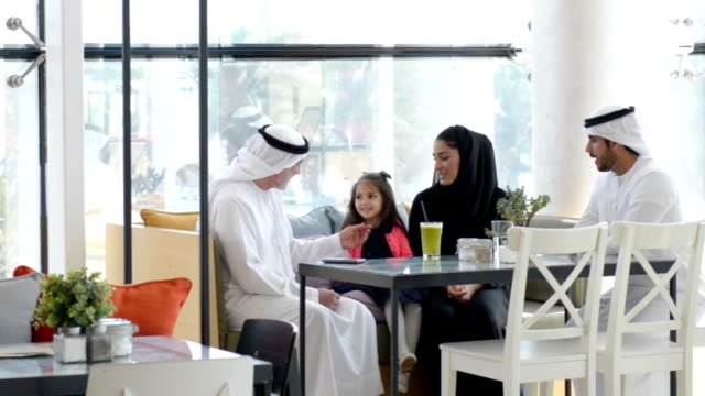 Three-generation Emirati family at cafe