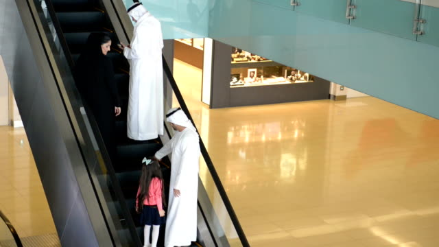 Three-generation Emirati family on escalator
