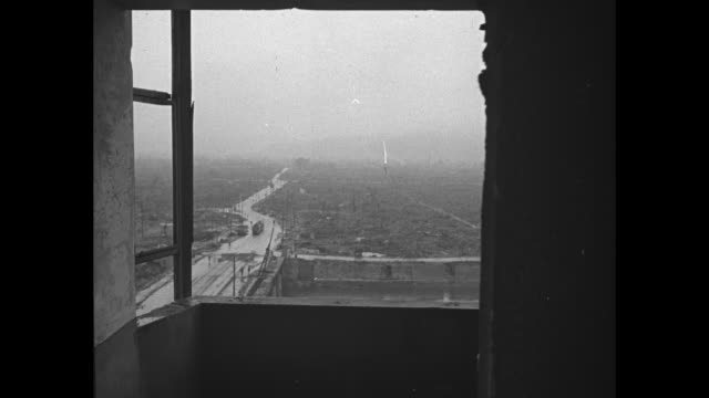 POV through destroyed window of destruction in Hiroshima with haze over landscape and river at left / LS the city as seen through another blownout...