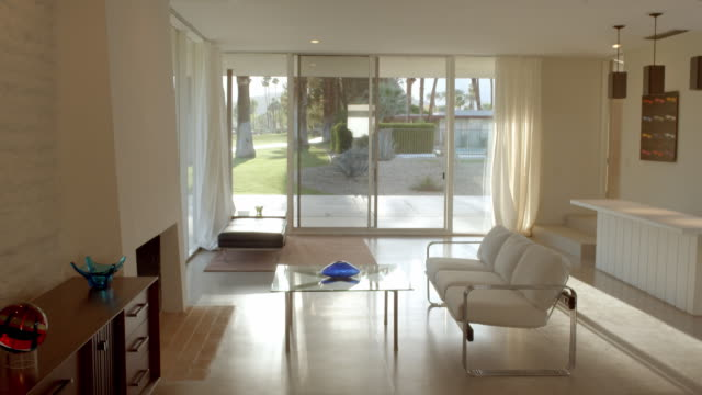 TS through interior mid-century modern white living room with glass door sliders and a view of country club golf course