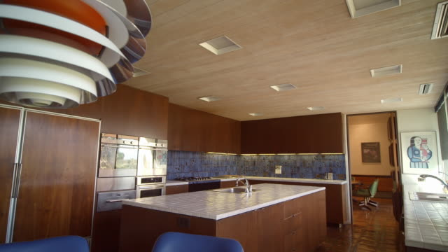 DS through mid-century modern kitchen in country club home from 1971 with space age kitchen lamp, white tiled counter tops, wood paneled kitchen cabinets and built-ins