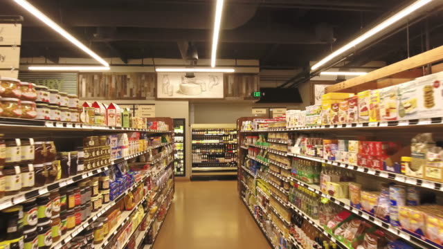 DS through supermarket aisle with international and organic foods on shelves an alcoholic beverages in refrigerated displays
