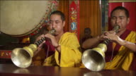 Tibetan Buddhist monks play traditional horns at the Sakya Center in Dehradun, India. Available in HD.