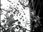 ticker tape falling from above / crowds tossing ticker tape and holding newspapers