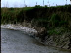 A tidal bore forms on the River Severn where it swells over the grassy banks.