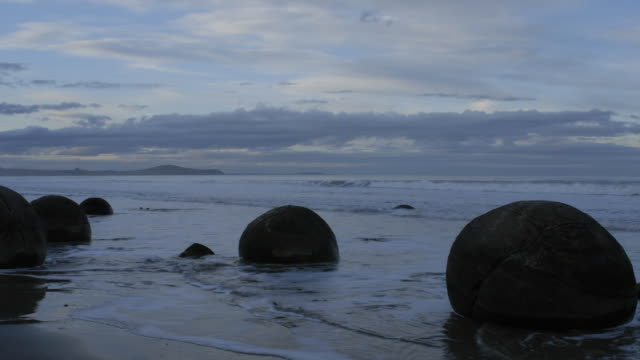 A tide ebbs and flows past large round boulders. Available in HD.
