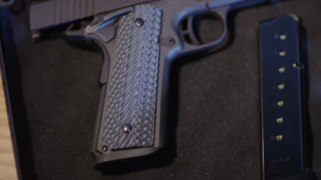 Tight of a semi-automatic pistol and ammunition clip laying in a case.