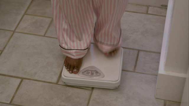Tight shot of a woman's feet as she weighs herself in the bathroom.