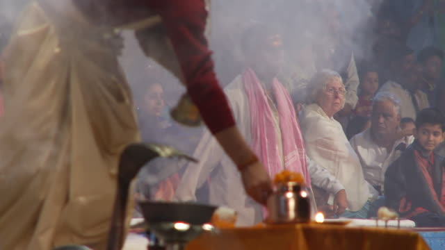 Tight shot of an incense offering to the Ganges, and a gathered crowd behind.