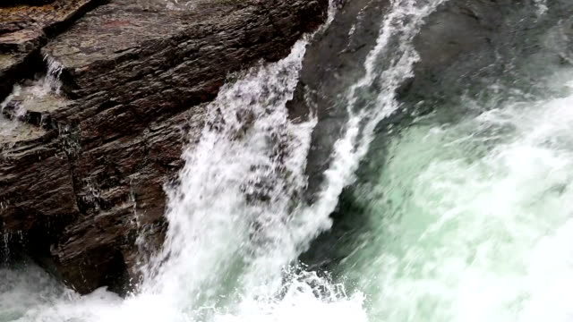 Tight shot pan right then left of water rapids cascading over lichen covered rocks.