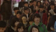 Tight slow motion shot of crowd walking down the street in Seoul