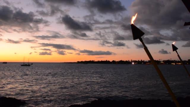 Tiki fire light over Ocean at Kailua-Kona beach at sunset