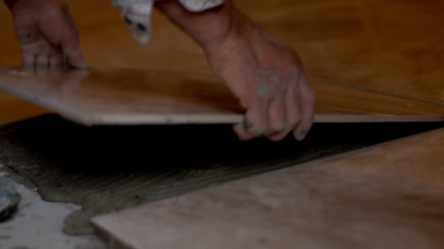 Tiler laying a tile on the floor