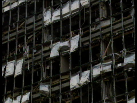Tilt down and zoom out from building damaged in IRA Docklands Bombing to press covering the incident 10 Feb 96