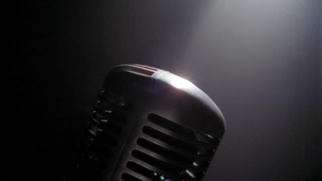 Tilt down close up microphone in spotlight