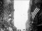 B/W 1927 tilt down confetti falling over marching band in ticker tape parade for Lindbergh / newsreel