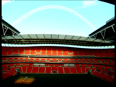 Tilt down from arch against blue sky to pitch and seats inside Wembley Stadium London