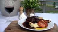 tilt down from coastal view out of restaurant window to RibEye Black Angus on the bone with mash grilled tomato and jus Salt and pepper shakers stand...