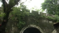 Tilt down from crenellations to car and bicycles travelling through arch in ancient city walls