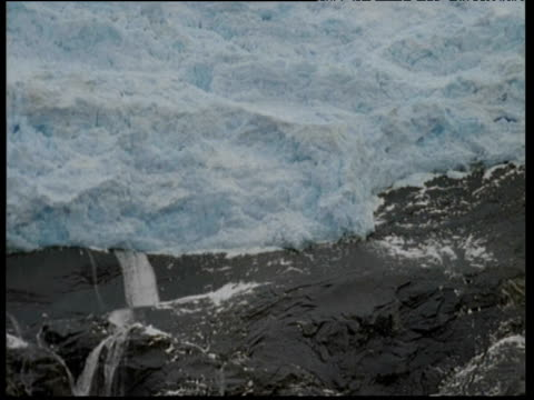 Tilt down from ice shelf to waterfalls running over black rock covered lightly in snow