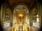 Tilt down from ornate ceiling and fresco of Madonna and Child above altar in Russian Orthodox Church