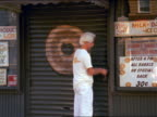 tilt down from sign on bagel shop to white-haired man unlocking chain + lifting metal gate / NYC