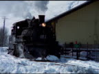 Tilt down from snow covered mountain to steam train moving slowly along tracks, Durango