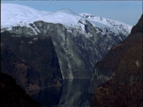 Tilt down from snow-capped mountain to dark fjord waters