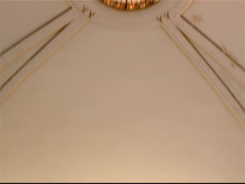 Tilt down from stained glass skylight inside Baptist church to view of pews from behind pulpit