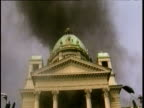 Tilt down from thick black smoke emitting from Parliament roof to thousands of Serbian protestors outside building entrance Belgrade; 05 Oct 00