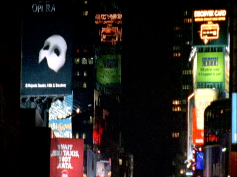 Tilt down from top of Times Square buildings to show street activity including flashing lights billboards and traffic New York City