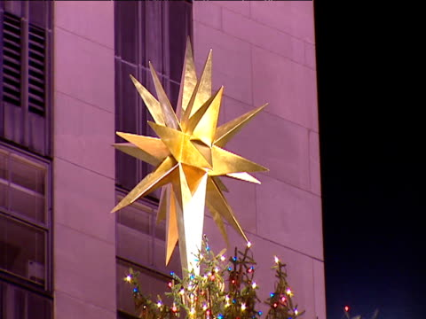 Tilt down large Christmas tree with star on top at Rockefeller Center