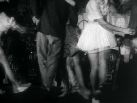 B/W 1938 tilt down legs of teens swing dancing + kicking / big band in background / documentary