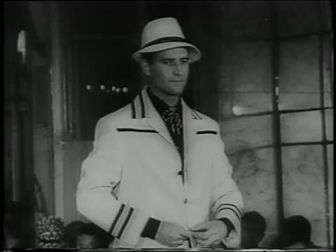 B/W 1961 tilt down man in hat trimmed white suit on runway in Italian fashion show