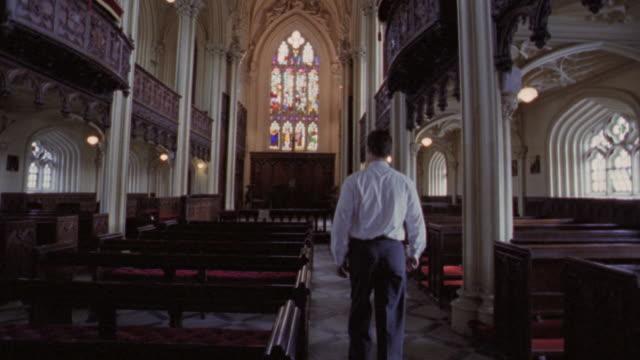 REAR VIEW tilt down man walking down aisle of church + sitting in pew / Dublin, Ireland