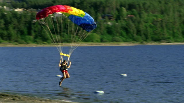 tilt down man with parachute landing roughly in lake then standing up / near Stavanger, Norway