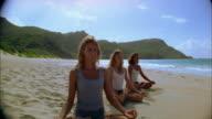 Tilt down medium shot women sitting cross-legged while doing yoga on beach