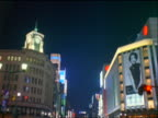 tilt down neon lights + people crossing street in Ginza district of Tokyo at night / Japan