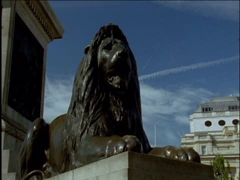 Tilt down over lion statue Trafalgar Square London