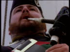 Tilt down over man in military uniform playing bagpipes at Canada Day celebration
