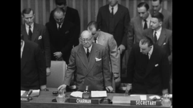 Tilt down pan delegates stand in moment of silence in memoriam for Soviet premier Joseph Stalin / Tilt down Joao Muniz of Brazil UN chairman of the...