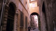 tilt down priest carrying Bible walking bicycle toward + past camera in alley / Rome, Italy