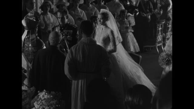 tilt down MS Prince Rainier walks into Saint Nicholas Cathedral and down aisle / Grace Kelly waits at altar in front of chairs as Bishop Giles Barthe...