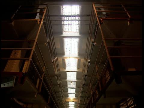 Tilt down prison balconies to dimly lit prison corridor. Cells either side Alcatraz
