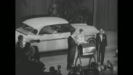 Tilt down shot Grace Kelly her fiance Prince Rainier and the emcee of the 'Imperial Ball A Night in Monte Carlo' charity event stand on a stage in...