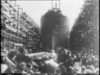 Tilt down shot of USS Iowa Battleship in shipyard / 65000 tons surpassing next largest warship by 10000 / Eleanor Roosevelt walks past camera smiling...