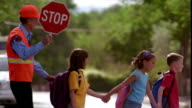 PAN tilt down three children holding hands + crossing street with senior crossing guard holding stop sign