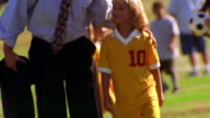 MS tilt down tilt up businessman kissing girl in soccer uniform / they walk on field toward camera